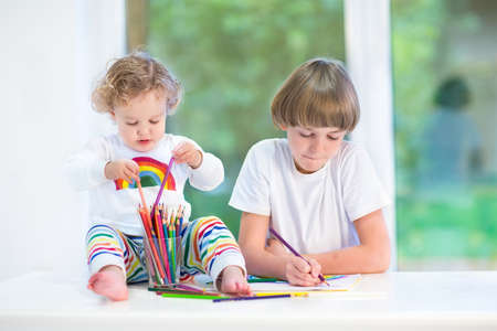 Funny toddler girl playing with colorful pencils sitting on a white desk next to a window watching her brother drawing