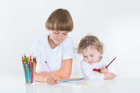 Brother and toddler sister painting together at a white desk  photo