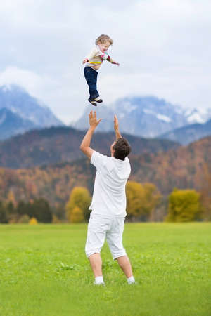autumn trees: Young father throwing his baby daughter high in the sky with beautiful autumn trees and snow covered mountains  Stock Photo