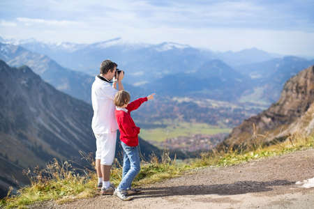 Young father and his teenager son taking pictures of a beautiful valley in the mountains  photo