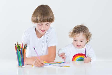 Portrait of a school boy painting at a white desk and his little sister helping him  photo