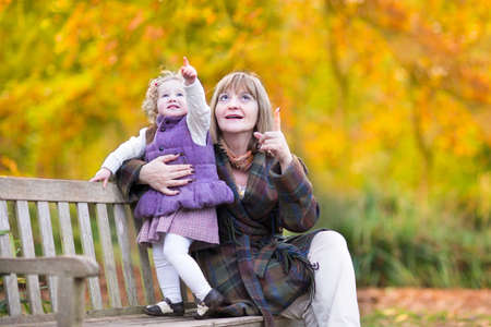 Beautiful lady playing with a little toddler girl on a wooden bench in an autumn park with colorful yellow trees  photo