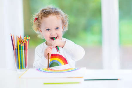 Funny laughing baby girl drawing with colorful pencils at a white desk next to a big window into the garden  photo