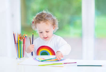 Sweet funny toddler girl painting a rainbow in a white room with a big window into the garden  photo