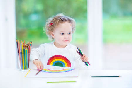 Funny smiling toddler girl drawing a rainbow with colorful pencils at a white desk sitting next to a big window into the garden with green trees  photo