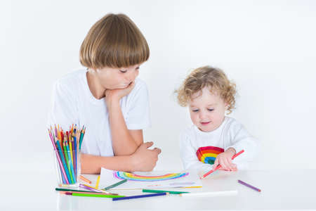 Cute toddler girl drawing with colorful pencils and her brother watching and smiling  photo