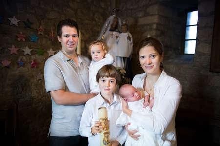 baptism: Felice giovane famiglia con tre bambini celebrare il battesimo del loro bambino appena nato