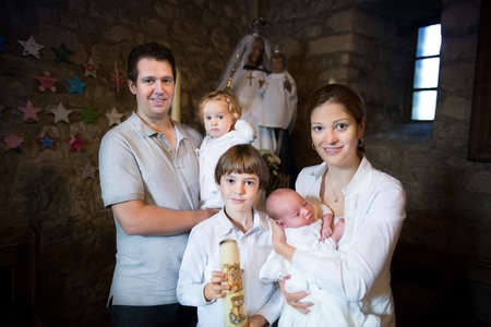 Happy young family with three children celebrating the baptism of their newborn baby