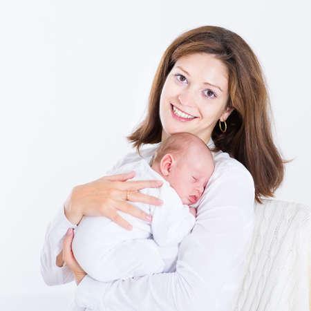 newborn: Young mother holding her sleeping newborn baby