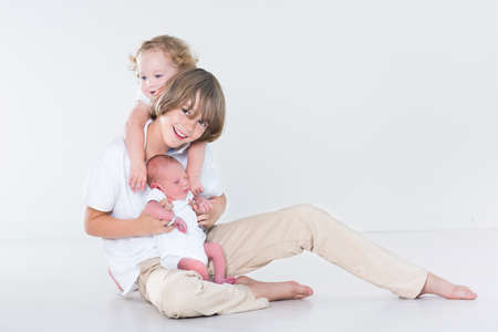 Three beautiful children - teenager boy, toddler girl and a newborn baby - playing together in a white room  photo