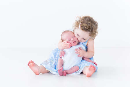 Sweet toddler girl kissing her newborn baby brother  photo