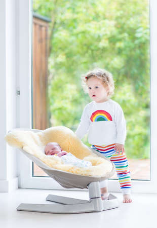 Cute toddler girl playing with her newborn baby brother relaxing in a swing next to a big window and door to the garden  photo