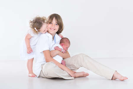 Happy laughing boy and his adorable toddler sister playing with their newborn baby brother  photo