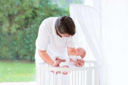 bassinet: Young father putting his newborn baby into a white round crib with canopy next to a big window into the garden with green trees