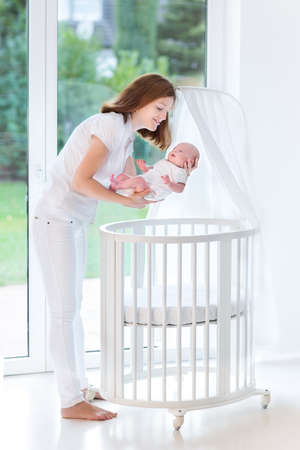 baby crib: Young mother putting her newborn baby to sleep in a white round crib with canopy next to a big window