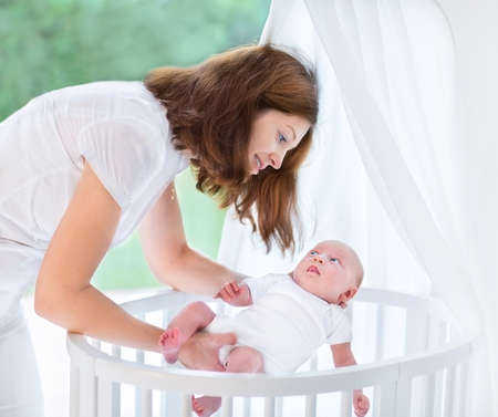 Young beautiful mother putting her newborn baby into a white round crib with canopy next to a big window