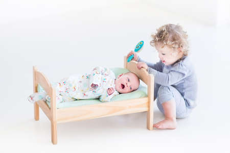 brothers and sisters: Funny curly toddler girl playing with hew newborn baby brother