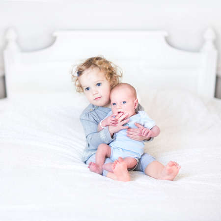 new born baby: Cute toddler girl playing with her newborn baby brother