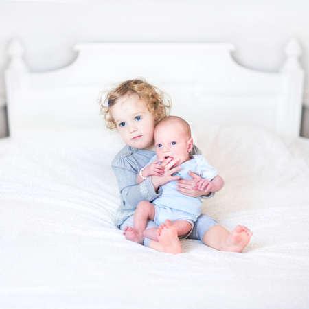 Het leuke peutermeisje spelen met haar pasgeboren broertje