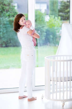 bassinet: Young mother holding her newborn baby standing at a white crib next to a big window  Stock Photo