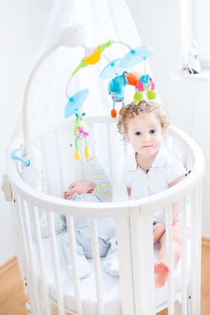 baby crib: Cute funny toddler girl sitting in a crib of her her newborn baby brother with colorful toys and canopy  Stock Photo