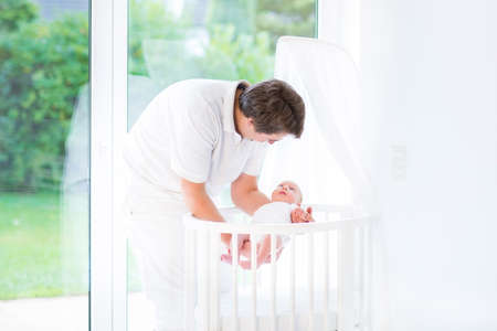 bassinet: Young smiling father putting his newborn baby in a white round bassinet at a big window to the garden