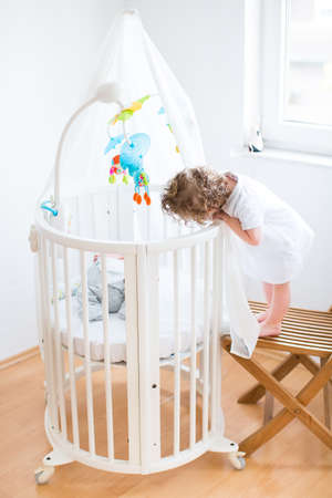 Funny curly toddler girl looking at her newborn baby brother sleeping in a white round crib & Portrait Of A Newborn Baby Boy Sleeping In A White Round Crib ...