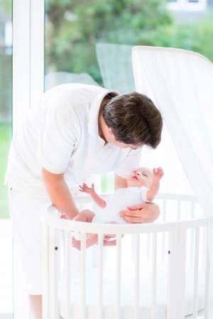bassinet: Happy young father putting his smiling baby in a white round crib next to a window