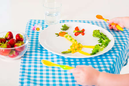 eating right: Healthy vegetarian lunch for little kids, vegetables and fruit served as animals, corn, broccoli, carrots and fresh strawberry helping children to learn eating right and clean, child