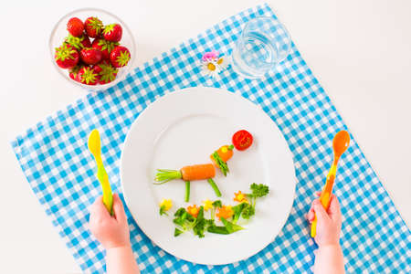 Healthy vegetarian lunch for little kids, vegetables and fruit served as animals, corn, broccoli, carrots and fresh strawberry helping children to learn eating right and clean, child