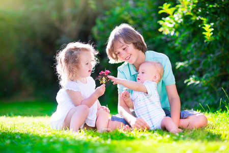 sister and brother: Three happy kids, brothers and sister, laughing teenager boy, little baby and a funny curly girl playing together with flowers in a sunny garden of their backyard  on a warm sunny day