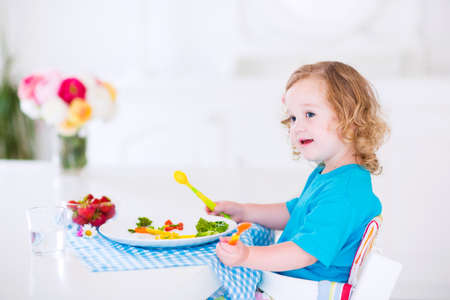 eating right: Happy little girl, cute curly toddler, eating fresh vegetables for lunch, healthy salad snack, corn, broccoli, carrots and strawberry fruit in a white dining room sitting in a high chair