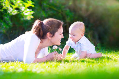 family grass: Happy beautiful woman, young mother playing with her adorable baby son, cute little boy, enjoying together a sunny warm day playing on the lawn in a summer garden