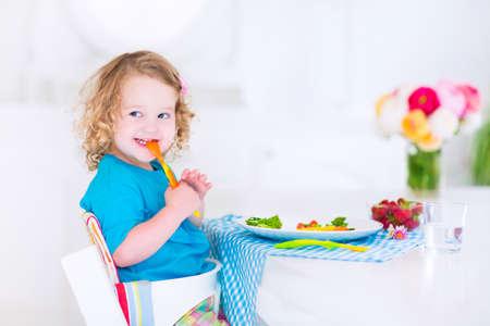 Niña feliz, niño lindo rizado, comer verduras frescas para el almuerzo, ensalada merienda saludable, maíz, brócoli, zanahorias y fruta de la fresa en un comedor blanco, sentado en una silla alta