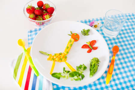 eating right: Healthy vegetarian lunch for little kids, vegetables and fruit served as animals, corn, broccoli, carrots and fresh strawberry helping children to learn eating right and clean Stock Photo