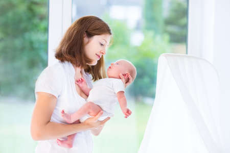 Beautiful young mother and her newborn baby at a big window in a white bedroom  photo