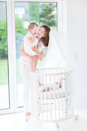 bassinet: Young happy mother showing her toddler daughter a newborn baby in a white round crib at a big window with garden view