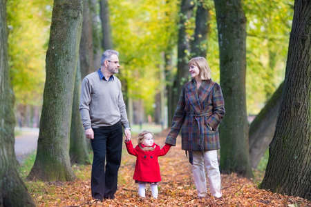 grand father: Happy laughing couple walking in an autumn park with a beautiful toddler girl in a red coat