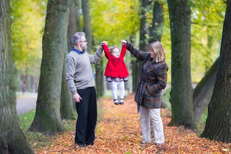 Happy family playing with a little toddler girl in an autumn park with beautiful yellow trees