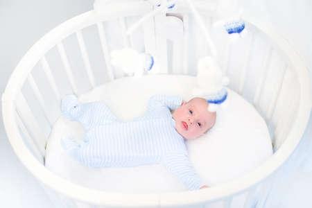 Cute newborn baby boy in a white round crib watching toys  photo