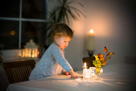 Cute toddler girl watching burning candles in a beautiful dark dining room  photo