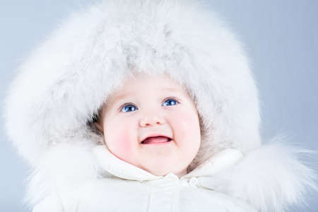 Happy laughing baby in a white winter jacket  photo