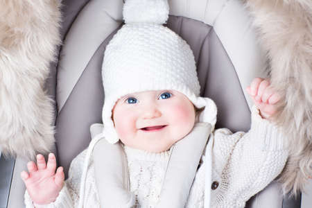buggy: Cute smiling baby sitting in a stroller on a cold winter day  Stock Photo