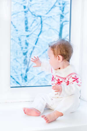 Cute baby in a knitted sweater with Christmas ornament sitting at a window watching snow covered trees  photo