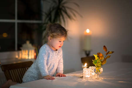 Portrait of a beautiful little girl watching candles in a dark dining room  Stock Photo