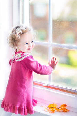 Laughing toddler girl watching out of the window in autumn