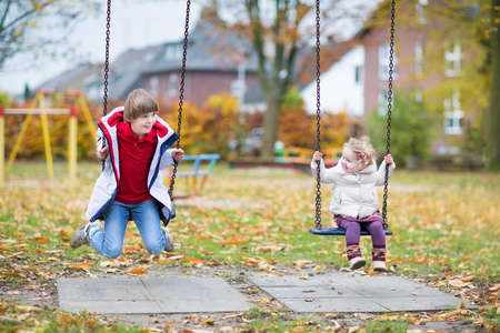 Happy laughing boy and his little baby sister playing together on a swing in autumn  photo