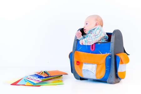 mochila escolar: Bebé recién nacido minúsculo en una mochila grande en el fondo blanco Foto de archivo