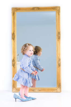 Cute toddler girl with beautiful curly hair wearing a blue dress is putting on her mother s high heels shoes standing at a big mirror with a wooden frame in a white bedroom at home