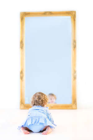 Funny toddler girl with beautiful curly hair wearing a blue dress watching her reflection in a mirror  photo